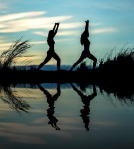 Two Woman Practicing Yoga by a Lake, What is Holistic Addiction Treatment, Foundations Wellness Center