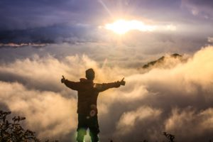Man with arms out and thumbs up looking at sunrise over the mountains and clouds, What an addiction counselor wishes you knew about your drug addict daughter or son, Foundations Wellness Center