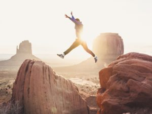 Man leaping between boulders, inpatient vs outpatient rehab, Foundations Wellness Center