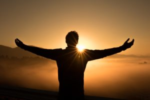 Man raising his arms in front of a sunset, how do you get an addict into treatment, Foundations Wellness Center