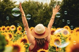 woman in a field of sunflowers, how much does drug rehab cost, how to find an affordable rehab, Foundations Wellness Center