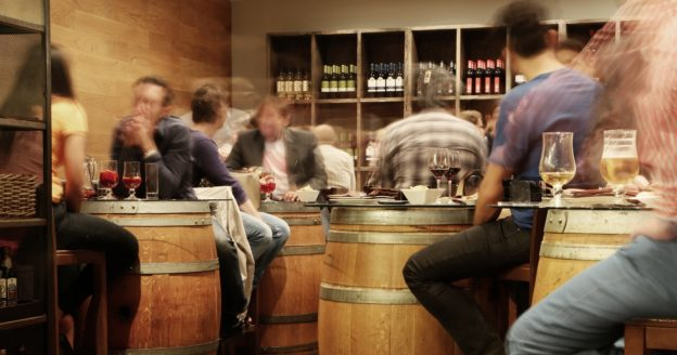 Blurred photo of people at a bar, How Long Does Alcohol Stay in Your System, Foundations Wellness Center