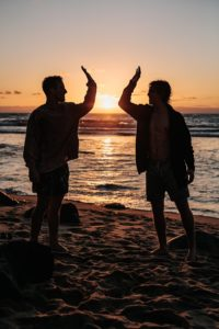 Two Men High Fiving on the Beach, Overcoming Addiction, Foundations Wellness Center