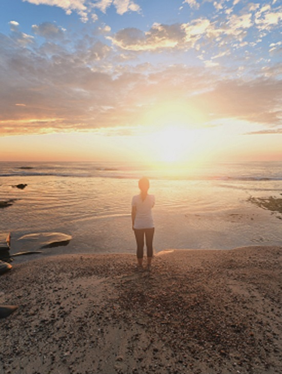 woman looking at sunrise on the beach, medication assisted treatment, Foundations Wellness Center