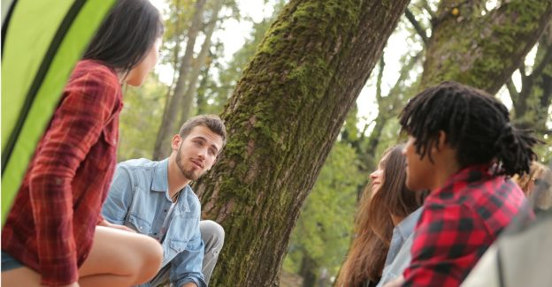 man talking with three other people camping in a forest, what is an addictive personality, Foundations Wellness Center