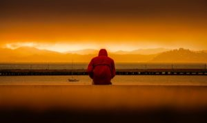 person-wearing-red-hoodie-sitting-in-front-of-body-of-water, what is an addictive personality, Foundations Wellness Center