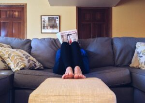 Person hiding behind a magazine while sitting on the couch, what is post acute withdrawal syndrome and how to deal with it