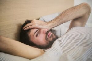 pensive-man-lying-in-bed, what is post acute withdrawal syndrome and how do I deal with it