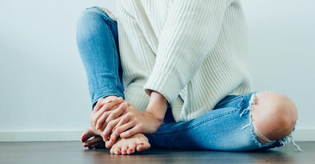 woman in holy jeans and white sweater sitting on a hardwood floor, Baker Act, Foundations Wellness Center