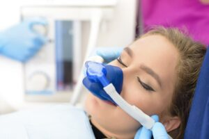 Laughing gas used in a medical procedure, woman with mask on and eyes closed