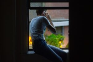 man leaning out window talking on phone, 8 lies addicts tell, Foundations Wellness Center