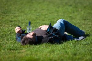 man passed out in a grassy field next to a liquor bottle, whippets and alcohol increase the risk
