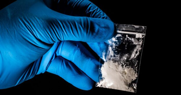 Blue gloved hand holding small bag of fentanyl, Fentanyl fueled increase in overdose deaths, COVID