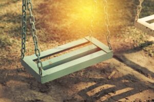 Sunbeam shining on an empty swing on a playground, fentanyl drives record overdose rate, COVID is a contributor
