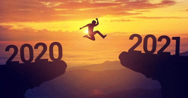 Man jumping from one cliff with 2020 to another that reads 2021 with sunset in foreground, new years resolutions harmful to your mental health