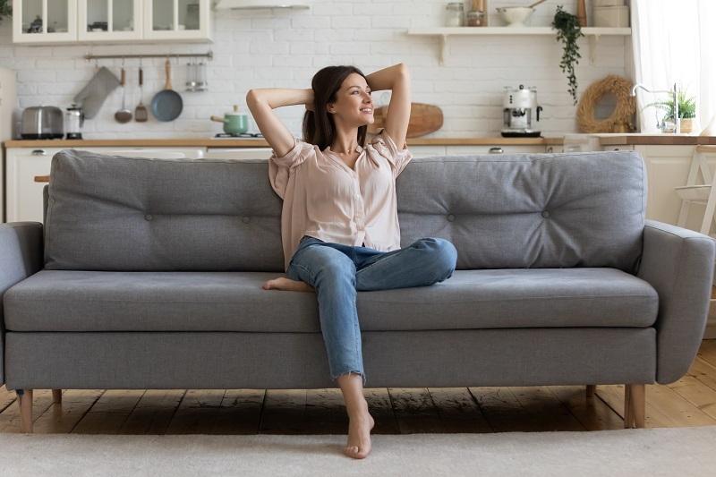 adult woman sitting on couch in front of kitchen in apartment, addiction treatment outcomes improve with age