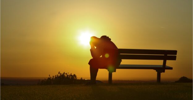 Person sitting on a bench with head in hands with sunset in background, co-occurring diagnosis and addiction, Foundations Wellness Center