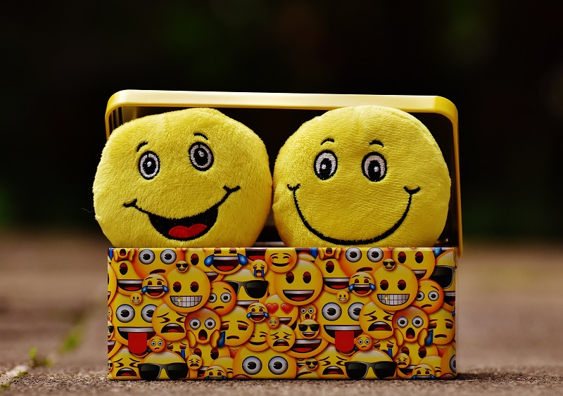 Two stuffed smiley faces peeping out of a box wrapped in smiley faced paper, ism addiction self medication