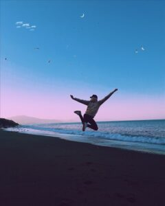 silhouette of person jumping with hands in the air against a background of the coastline at dusk, is addiction self medication, Foundations Wellness Center