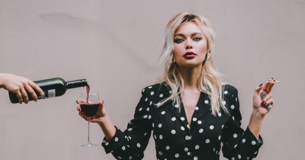 Woman in polka dot dress holding a wine glass that alcohol and being poured into and smoking, new study shows polysubstance users have poorer addiction treatment outcomes