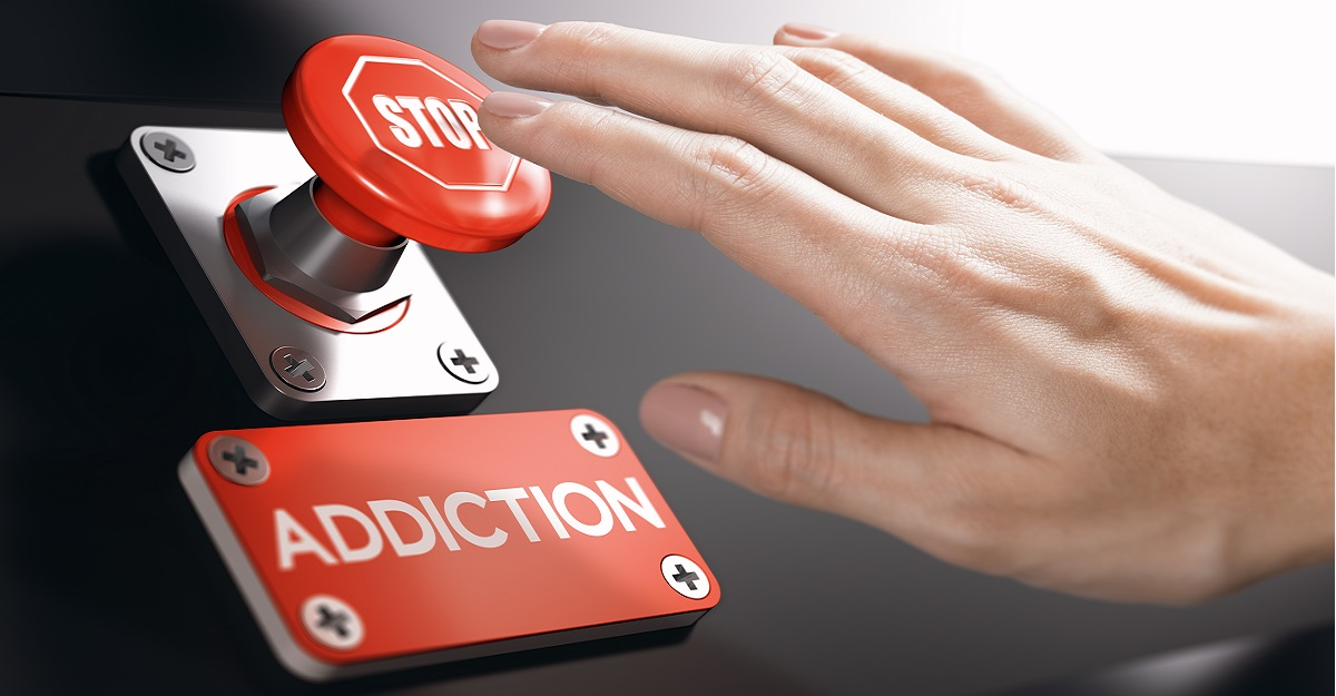 Hand above a stop button with a nameplate below it that reads addiction, Long Term Addiction Treatment Leads to better Outcomes, Foundations Wellness Center