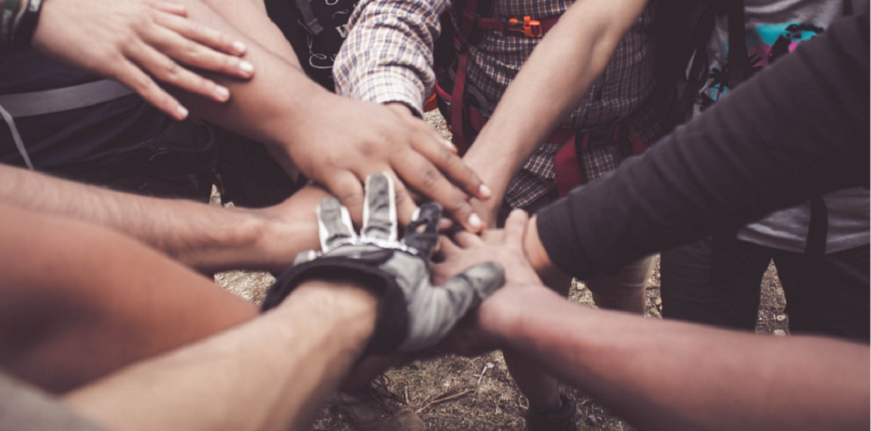 Circle of people with one hand touching in the middle, Long term addiction treatment leads to better outcomes, Foundations Wellness Center