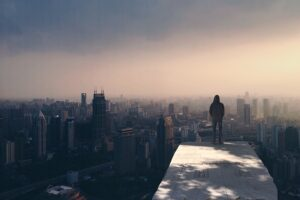 Person standing on a ledge high above a city, addiction myths