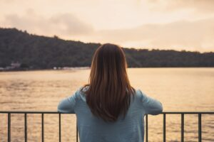 back of a person with long hair looking out at a waterway from a balcony, addiction myths