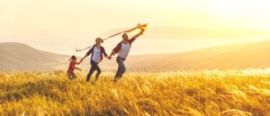 family running through a field with a kite against a moutainous background, addiction myths, Foundations Wellness Center