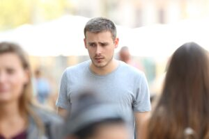 man looking distraught in a crowd of people, addiction myths