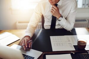 person in a business suit adjusting tie while sitting at a desk, addiction myths
