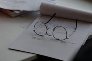 glasses-on-top-of-a-tablet-of-paper-on-a-desk-going-back-to-work-after-rehab-Foundations-Wellness-Center