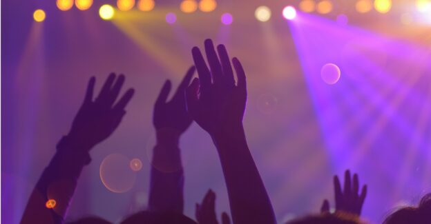 Arms Hands raised in a nightclub with purple and orange lights, is molly addictive, Foundations Wellness Center