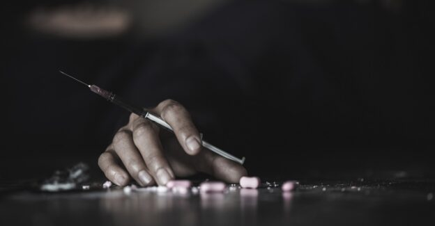 Hand-holding-syringe-resting-on-pills-on-a-table-with-dark-background-Overdose-after-Relapse-Foundations-Wellness-Center.jpg