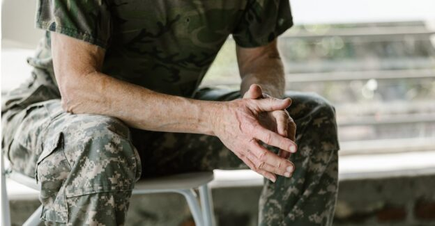 Man in fatigues sitting down with hands clasped together, PTSD, alcohol abuse and veterans, Foundations Wellness Center