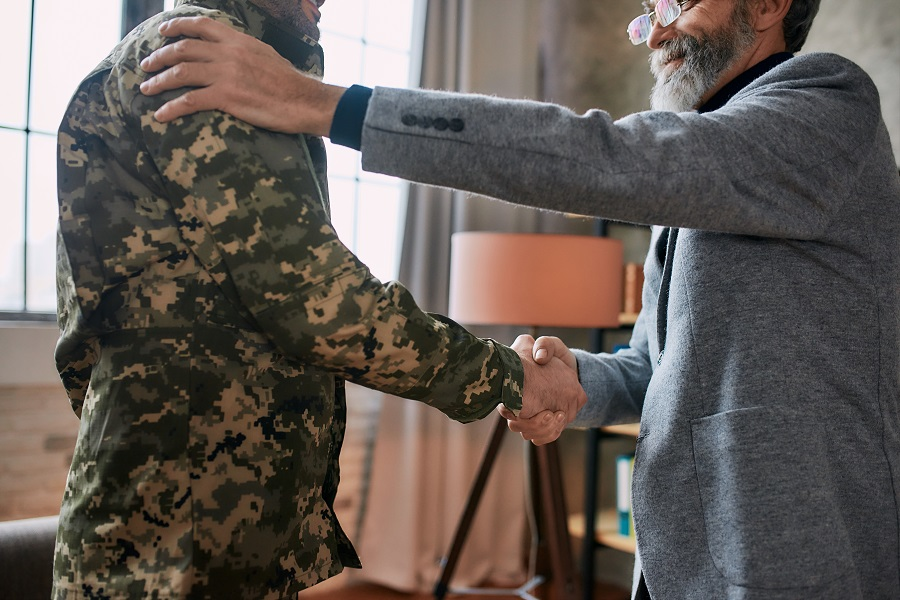 person-in-military-fatigues-shaking-hands-with-therapist-PTSD-alcohol-veterans-Foundations-Wellness-Center
