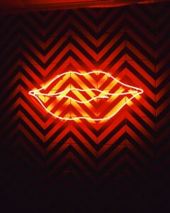 red neon lighted lips on a patterned wall, is Molly addictive, Foundations Wellness Center