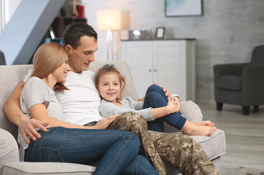 veteran-and-family-smiling-on-a-white-couch-PTSD-alcohol-veterans-Foundations-Wellness-Center